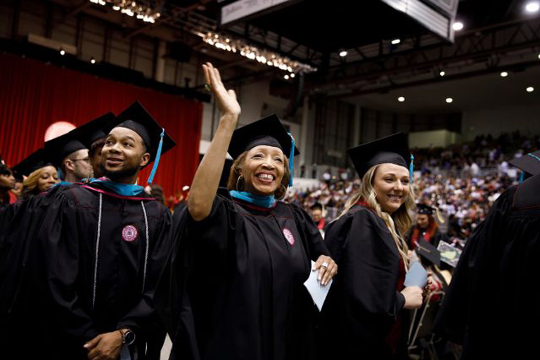 A graduate waves to family in the audience during the Indiana University Northwest Commencement at the Genesis Convention Center in Gary on Thursday, May 10, 2018.