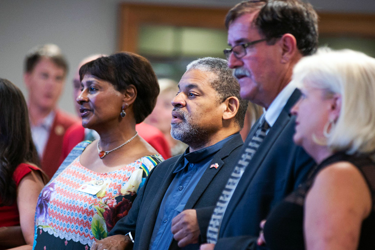 Alumni leaders link arms while singing IU's alma mater at the Alumni Association Board of Manager Pinning Ceremony in fall, 2019.
