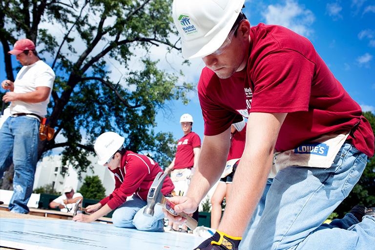 Alumni and students work together on a Habitat for Humanity house.